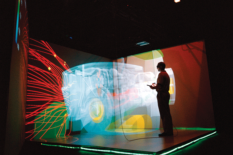 A man standing in a black room with holograms appearing on the stage.