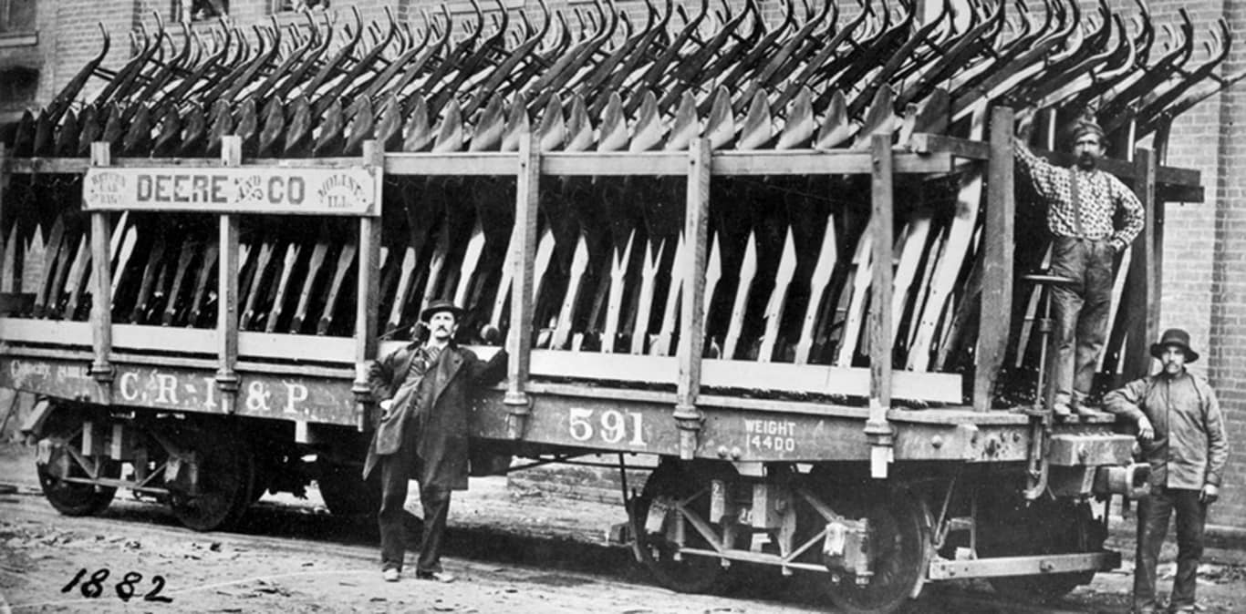 Gentlemen stand next to a trailer full of original plows